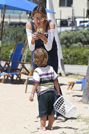 Alessandra Ambrosio is seen on the beach in Santa Monica with her son Noah, wearing Frame Denim Le High Flare stretch-denim overalls and Chanel flats. Her turquoise phone case is the Zero Gravity Oasis iPhone 6 Case - April 18, 2015
