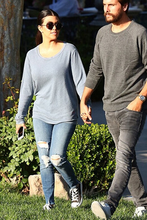 Kourtney Kardashian and partner Scott Disick head to dinner at Sushi restaurant Sugarfish on Monday night (May 18) in Calabasas, CA. Kourtney is wearing a Peace Love World top, Linda Farrow x The Row sunglasses, J Brand jeans in Fury and Converse.