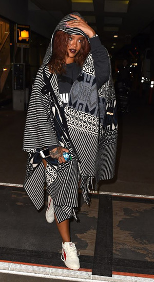 Rihanna wears a Chloe Hooded Geometric-Print Fringe Cape as she arrives back at LAX airport from her vacation in Hawaii on April 28, 2015.