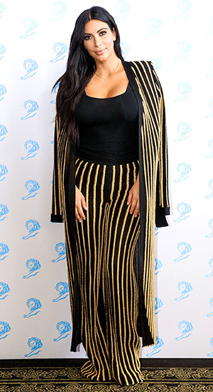 Kim Kardashian wearing a striped lurex cardigan and pants from Balmain to the Cannes Lions festival in France on June 24, 2015.