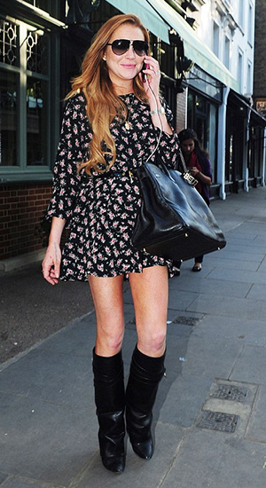 Lindsay Lohan chats on her phone in a Lisakai i Floral Dress and Givenchy Shark Lock Fold-Over Leather Boots outside The Ivy Garden in Chelsea, London on June 5, 2015.
