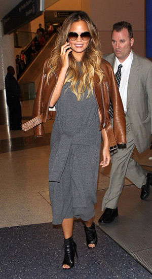 Chrissy Teigen wearing a Joseph Elle Tie Waist Dress touching down at LAX airport in Los Angeles, CA on August 17, 2015.