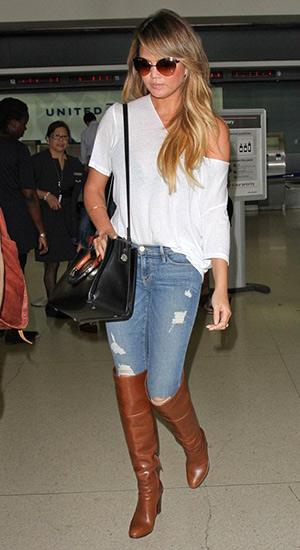 Chrissy Teigen carrying a The Row round handle tote, wearing Frame Denim jeans in Kitty Hawk and Chloé Glossed-Leather Over-the-Knee Boots arriving at LAX airport from Minneapolis on August 13, 2015 in Los Angeles, CA.