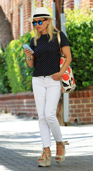 Reese Witherspoon stops by her office on July 28, 2015 in Los Angeles, CA wearing a Draper James hat, shirt, phone case, bag and pants. Her sunglasses are Illesteva and shoes are Paul Andrew Patmos Wedge Espadrilles.