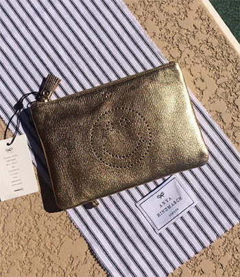 Anya Hindmarch Pale Gold Smiley Zip Top Pouch as seen on Kinsey Schofield Instagram.