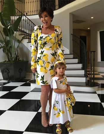 Kris Jenner poses in a Dolce & Gabbana Lemon Print Dress with her granddaughter Penelope.