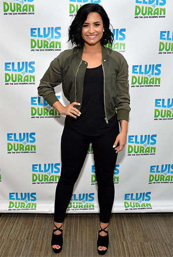 Demi Lovato wears a Rick Owens Palm Green Cropped Bomber Jacket and Aquazzura Kaya Leather and Suede Platform Sandals as she visits 'The Elvis Duran Z100 Morning Show' at Z100 Studio on July 13, 2016 in New York City.