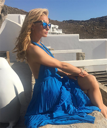 Paris Hilton wears a Anna Karin Karlsson Magpie Sunglasses and a Alice + Olivia Adalyn dress, July 2016.